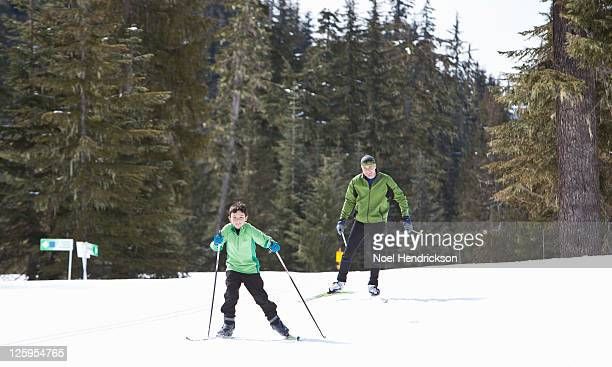 Tween boy leads his father on the ski trail