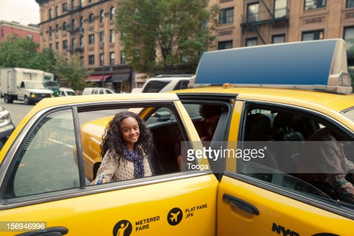 Tween girl getting into cab and smiling : ストックフォト