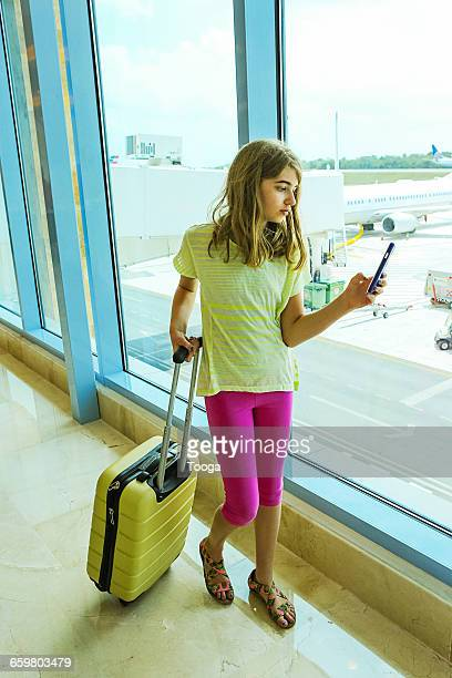 Tween girl looking at smartphone at airport