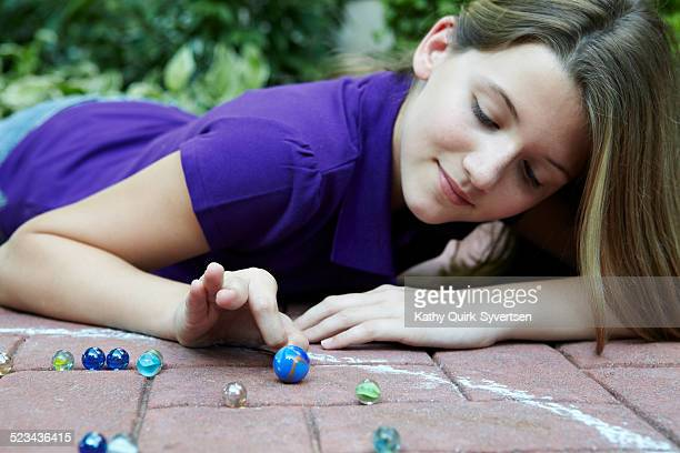Tween girl playing marbles