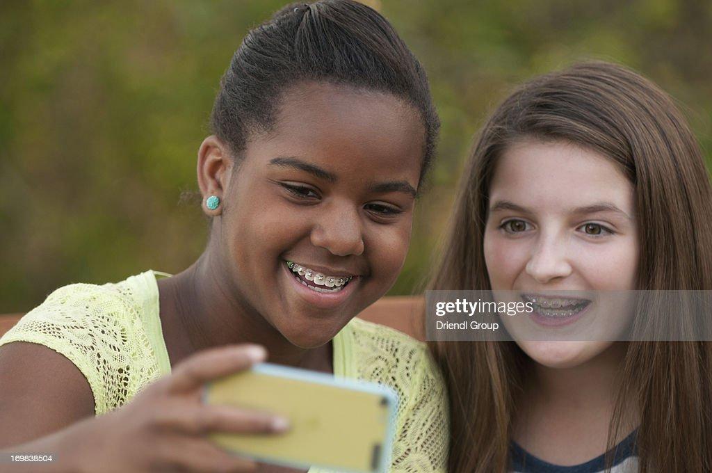 Tween girls taking Selfies with their smart phone. : Stock Photo