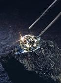 Tweezers above diamond on piece of coal, close-up