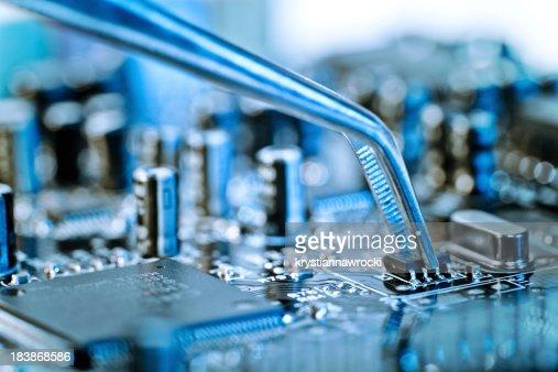 Tweezers grasping microchip on blue computer circuit board