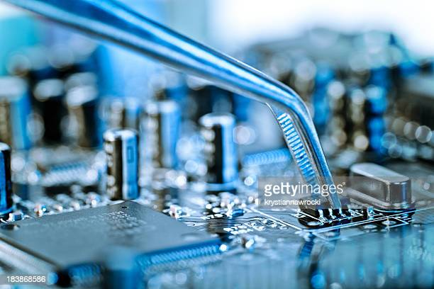 Tweezers grasping microchip on blue computer circuit board