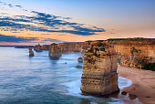 Twelve Apostles, Port Campbell National Park at sunset - Victoria, Australia. Sunlight hitting the rocks and sand creating a very sureal look.