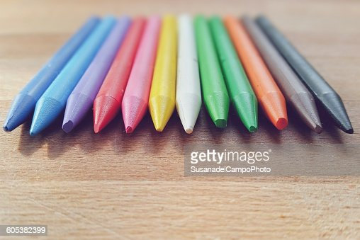 Twelve colored pencils lying on table