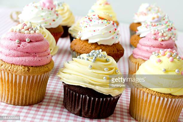 Twelve cupcakes with frosting and sprinkles on checker cloth