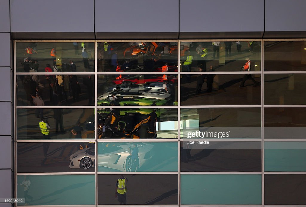 Twelve of the Lamborghini Aventador LP700-4 Roadsters are seen reflected in a window as people look at them as they are parked on the tarmac at the Miami International Airporton January 28, 2013 in Miami, Florida. The world wide unveiling of the new luxury super sports cars took place at the airport and included the vehicles being driven down the south runway of Miami International Airport.
