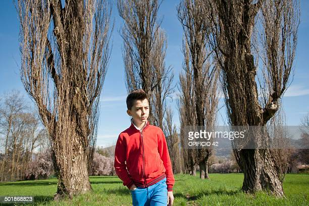 Twelve year old boy strolling along tree lined field