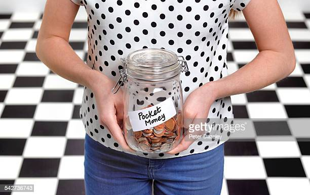 Twelve year old with pocket money in jar