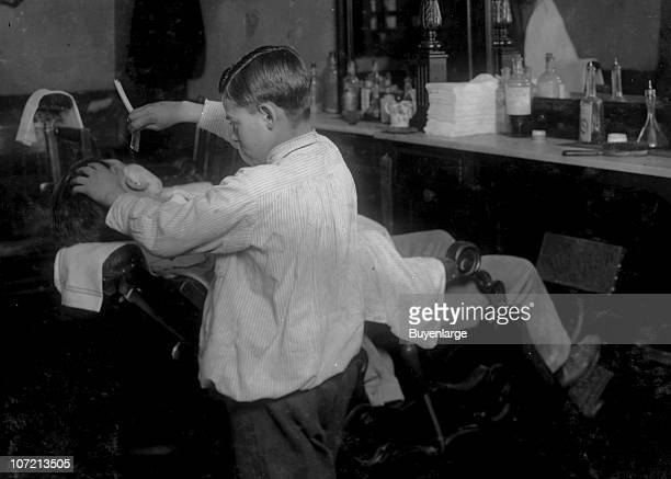 Twelveyearold barber Frank De Natale lathers and shaves a customer in his father's shop Boston Massachusetts 1917