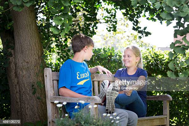 Twelveyearold girl and fourteenyearold boy sitting on a bench in a garden on August 11 in Duelmen Germany Photo by Ute Grabowsky/Photothek via Getty...