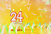 Twenty four years birthday. Cupcake with burning candles in the form of number 24. Bright yellow background with copy space