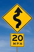 'Twenty MPH Curved Road Yellow Traffic Sign, Blue Sky Background'