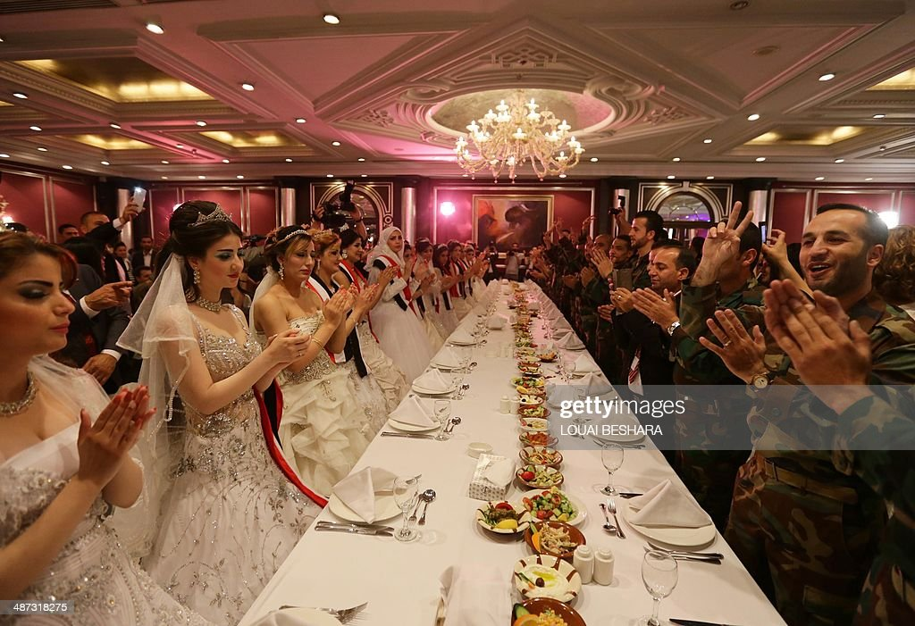 Twenty Syrian couples, made up of government soldiers and their brides, clap as they dance during a dinner following a group wedding ceremony in Damascus on April 29, 2014.