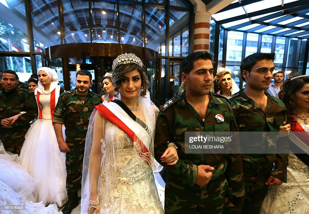 Twenty Syrian couples, made up of Syrian soldiers and their brides, pose for a photo following a group wedding ceremony in Damascus on April 29, 2014.