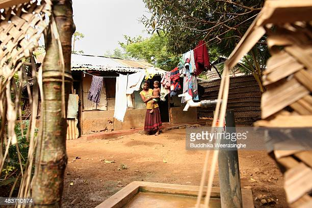 Twenty years internally displaced minority ethnic Tamil woman stands with her son in the IDP camp on August 122015 in Jaffna Sri Lanka The UN's Human...