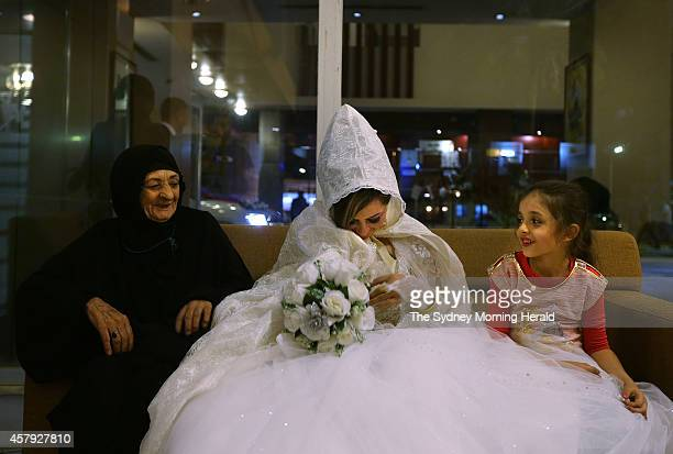 Twentyfouryearold bride Rasha Kareem shares a laugh with her new motherinlaw and niece after arriving at the Baghdad Hotel in the AlSadoon district...