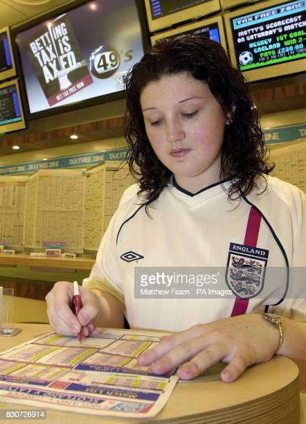 Twentyyearold England supporter Tina Morrow from Hackney east London takes advantage of Britain's new taxfree betting laws at Ladbrokes in London's...