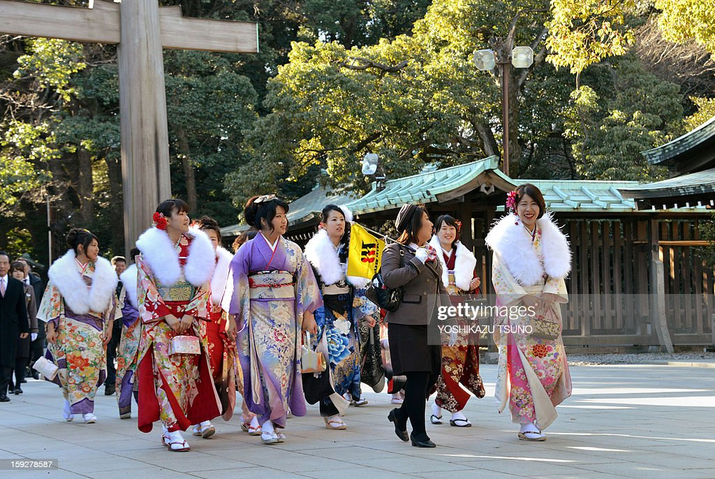 Twenty-year-old female tour guides dressed in traditional kimonos are led by a colleague (3rd R) as they visit Tokyo's Meiji Shrine to attend a purification ceremony with a Shinto priest to celebrate Japan's Coming of Age Day on January 11, 2013. Since tour guides will be busy working on Japan's national holiday Coming-of-Age Day on January 14, the company had a ceremony for them ahead of time. Young people turning 20 are officially recognised as adults in Japan. AFP PHOTO / Yoshikazu TSUNO