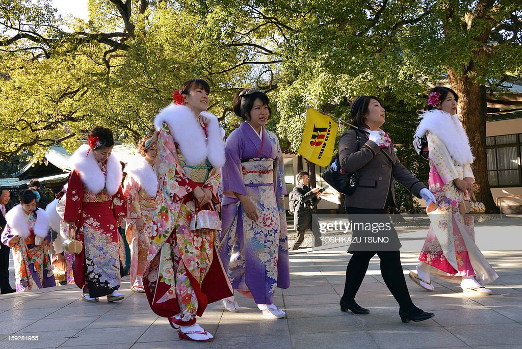 Twenty-year-old female tour guides dressed in traditional kimonos are led by a colleague (2nd R) as they visit Tokyo's Meiji Shrine to attend a purification ceremony with a Shinto priest to celebrate Japan's Coming of Age Day on January 11, 2013. Since tour guides will be busy working on Japan's national holiday Coming-of-Age Day on January 14, the company had a ceremony for them ahead of time. Young people turning 20 are officially recognised as adults in Japan. AFP PHOTO / Yoshikazu TSUNO