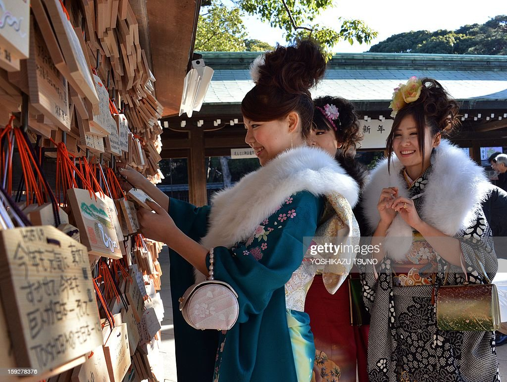 Twenty-year-old female tour guides dressed in traditional kimonos hang up 'ema', or voting tablets, with their written wishes at Tokyo's Meiji Shrine before attending a purification ceremony with a Shinto priest to celebrate Japan's Coming of Age Day on January 11, 2013. Since tour guides will be busy working on Japan's national holiday Coming-of-Age Day on January 14, the company had a ceremony for them ahead of time. Young people turning 20 are officially recognised as adults in Japan. AFP PHOTO / Yoshikazu TSUNO
