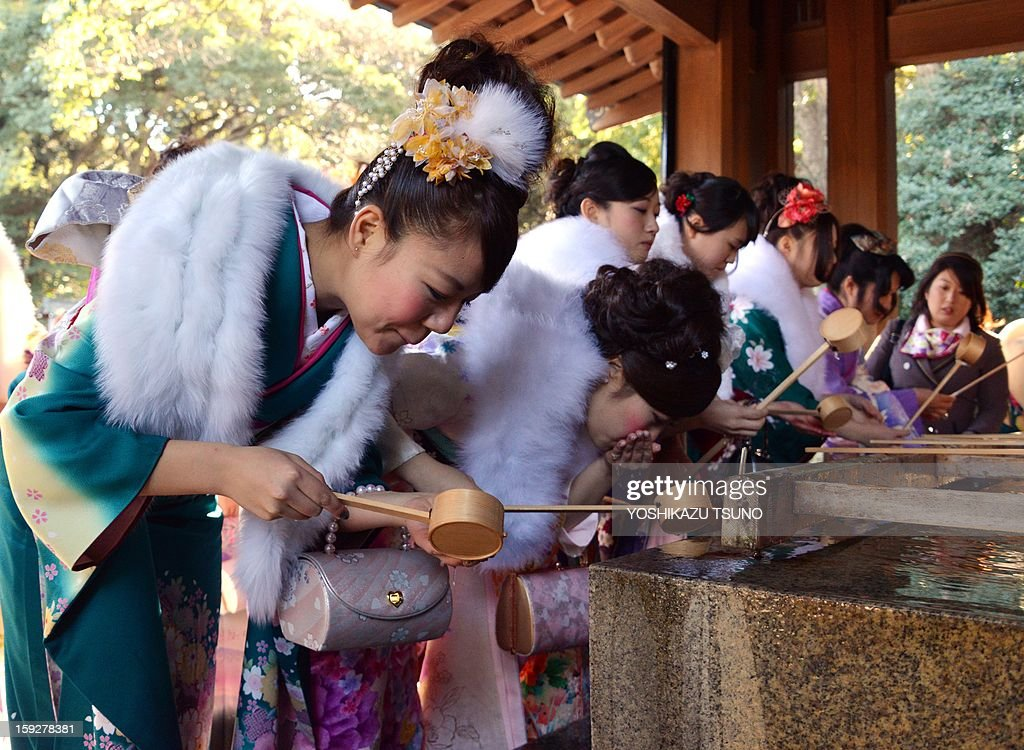 Twenty-year-old female tour guides dressed in traditional kimonos wash their mouths and hands at Tokyo's Meiji Shrine before attending a purification ceremony with a Shinto priest to celebrate Japan's Coming of Age Day on January 11, 2013. Since tour guides will be busy working on Japan's national holiday Coming-of-Age Day on January 14, the company had a ceremony for them ahead of time. Young people turning 20 are officially recognised as adults in Japan. AFP PHOTO / Yoshikazu TSUNO