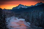Twilight at the 'Morant's Curve' offers a view of the frozen Bow River and the Canadian Pacific Railway at Banff National park near Lake Louise late...