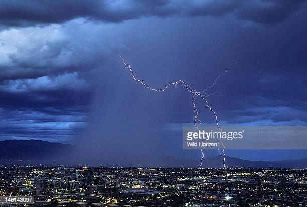 Twilight view just after sunset of forked ground discharge lightning as it leaps ahead of a rain shaft over city Tucson Arizona USA