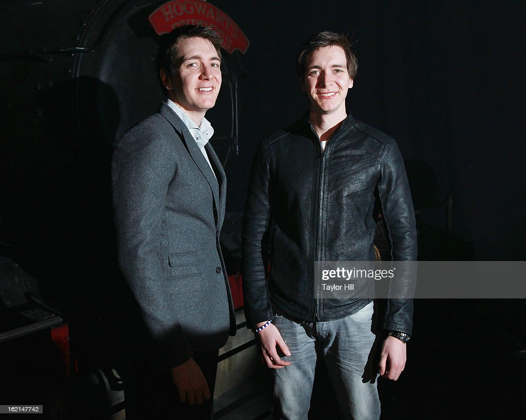 Twin actors Oliver Phelps and Jamie Phelps pose in front of the Hogwarts Express at Harry Potter:The Exhibition at Discovery Times Square on February 19, 2013 in New York City.