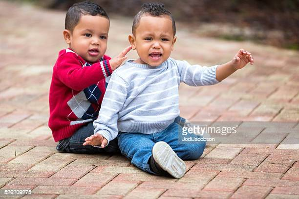 Twin African American toddler boys sitting on pavement