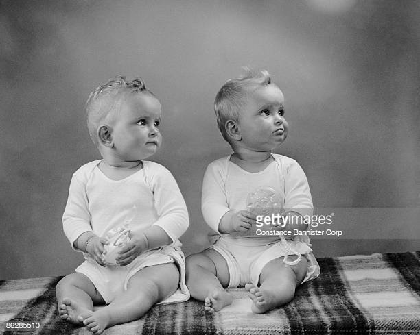 Twin babies sitting looking away in the same direction
