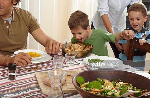 Twin boy pretending to eat chicken from bowl