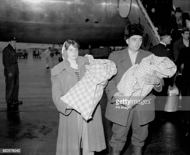 Twin boys born on October 23rd the day the Hungarian revolution started are carried by their parents from a BOAC Britannia on their arrival at London...