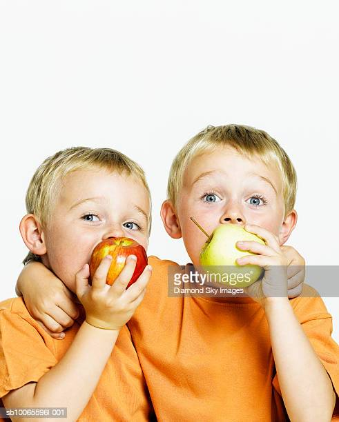 Twin boys (4-5) eating apples, close-up, portrait