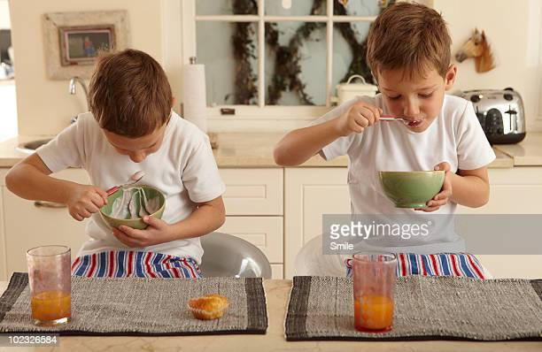 Twin boys eating same breakfast together