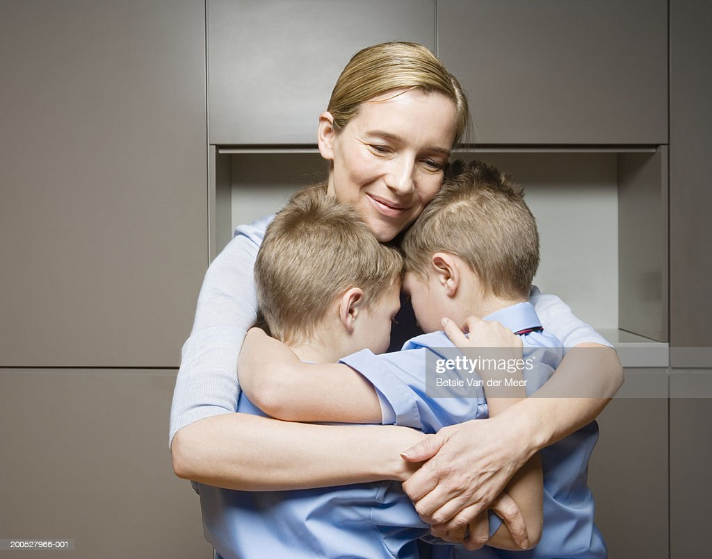 Twin boys (8-10) embracing mother, smiling : Stock Photo