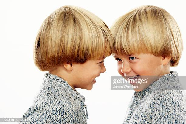 Twin boys (3-5) head to head, smiling, profile of one, close-up