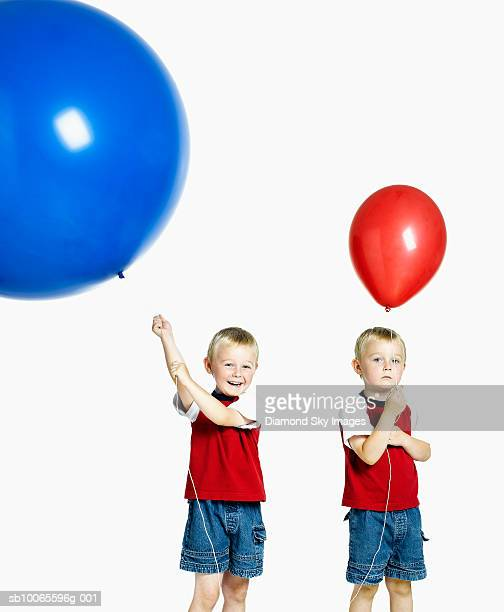 Twin boys (4-5) holding balloons, smiling, portrait