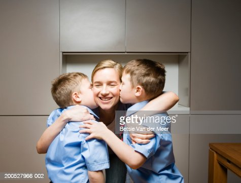 Twin boys (8-10) kissing mother, smiling : Stock Photo