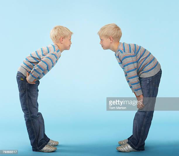 Twin boys looking at each other indoors