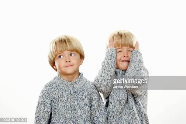 Zwei Jungen (3-5), mit Händen auf dem Kopf, anderen suchen