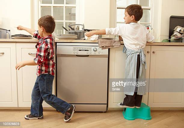 Twin boys passing cutlery while washing dishes
