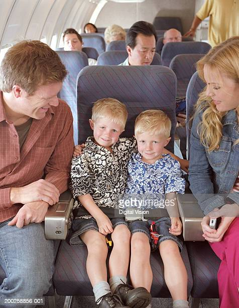 Twin boys (3-5) sharing seat between parents on aeroplane, smiling