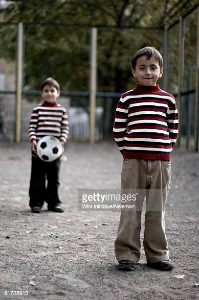 Twin boys standing together on playground, portrait