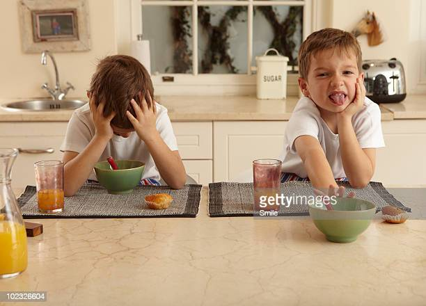 Twin boys unhappy with their breakfast