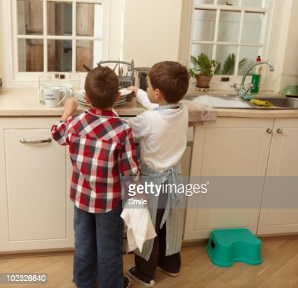 Twin boys washing the dishes after dinner : Stock Photo