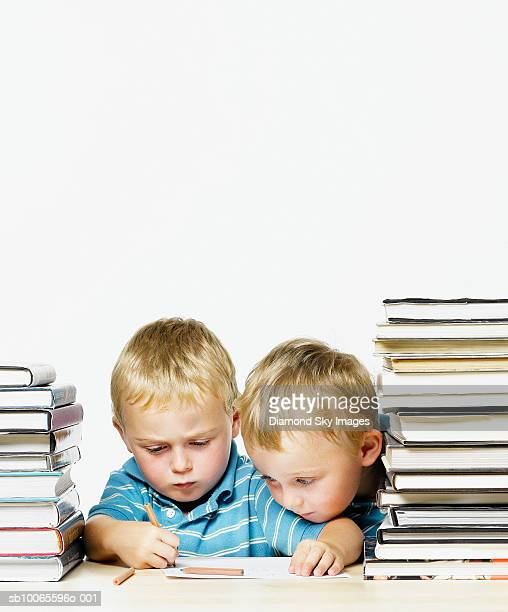 Twin boys (4-5) writing by stack of book