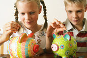Twin brother and sister (10-12) dropping coins into piggy banks, smiling, close-up