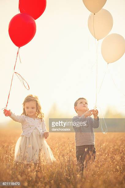 Twin brother and sister holding balloons outdoor